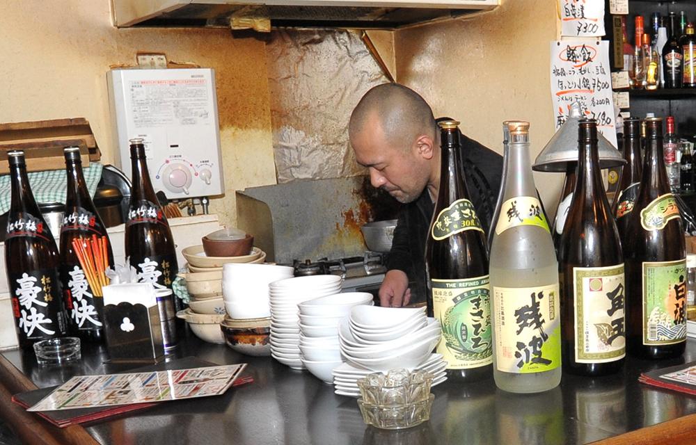 日本酒や泡盛の一升瓶がまさに「豪快」に並ぶカウンター。