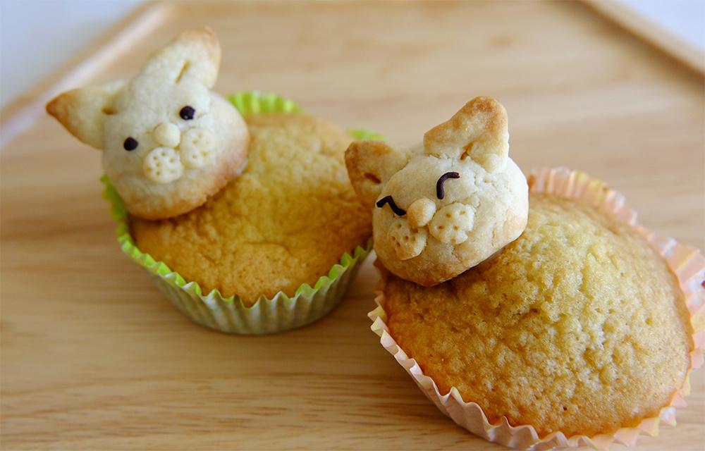 「猫カップ(350円)」。カップケーキの味はプレーンで、頭はクッキーで作られています。目は手描きのため、1つ1つ表情が異なります。「猫カップ」の売上の一部は、野良猫を殺処分から救う活動をしているボランティア団体に寄付されます。
