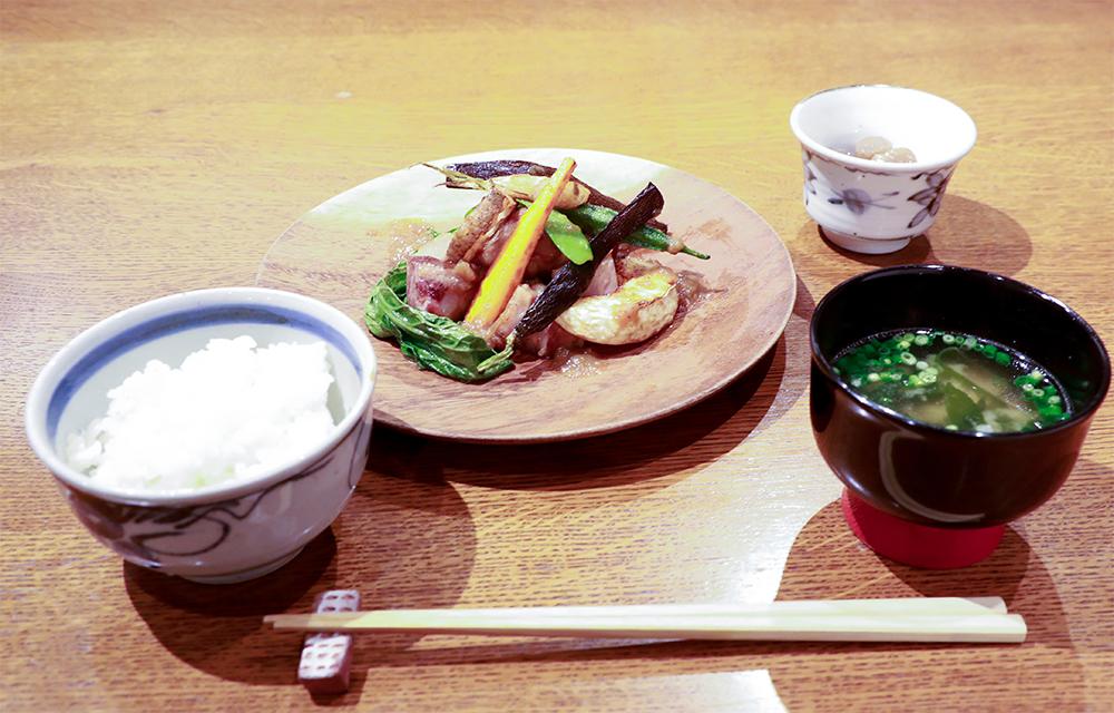 つやつやの炊きたてごはんと丁寧にだしをとったお味噌汁。ポークは焼き上げてから一口大にカットされ、グリルされたにんじん、ナス、絹さや、オクラ、小松菜などいろいろな野菜が添えられています。小鉢付き(980円)。