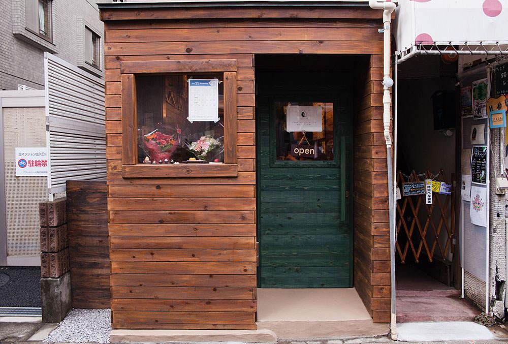 木造りの壁に小さな緑のドアが目印です。