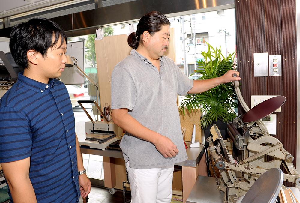 活版の印刷機「テキン」の使い方を中野さんがレクチャー中。