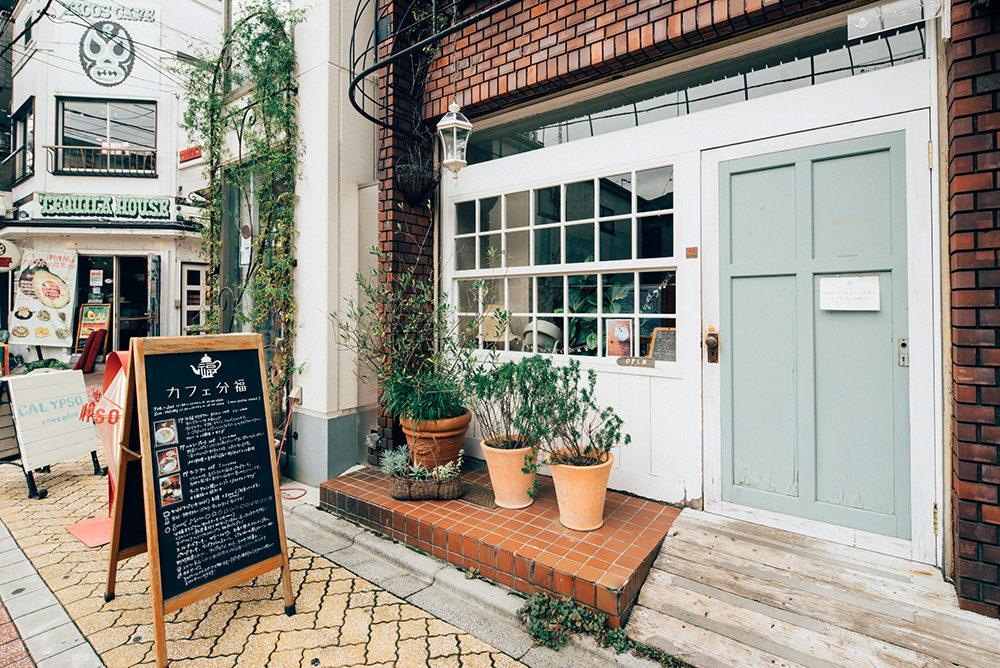 白い壁と薄いグリーンの扉が印象的なお店構え。